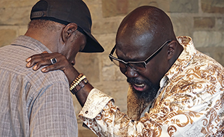 Pastor Payton praying with man