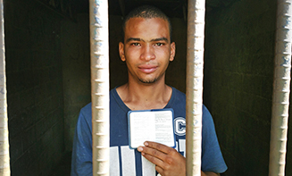 Carlos Daniel Vasquez in prison with a New Testament